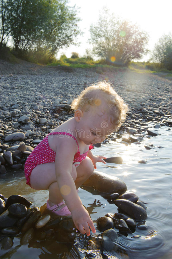 Cute baby girl playing with stones stock photo