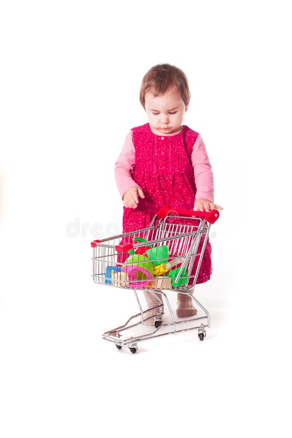 Cute baby girl playing with toy shopping cart. stock photo