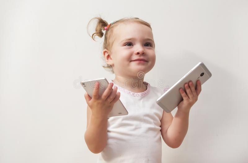 Cute baby girl playing with two mobile phones on white royalty free stock photo