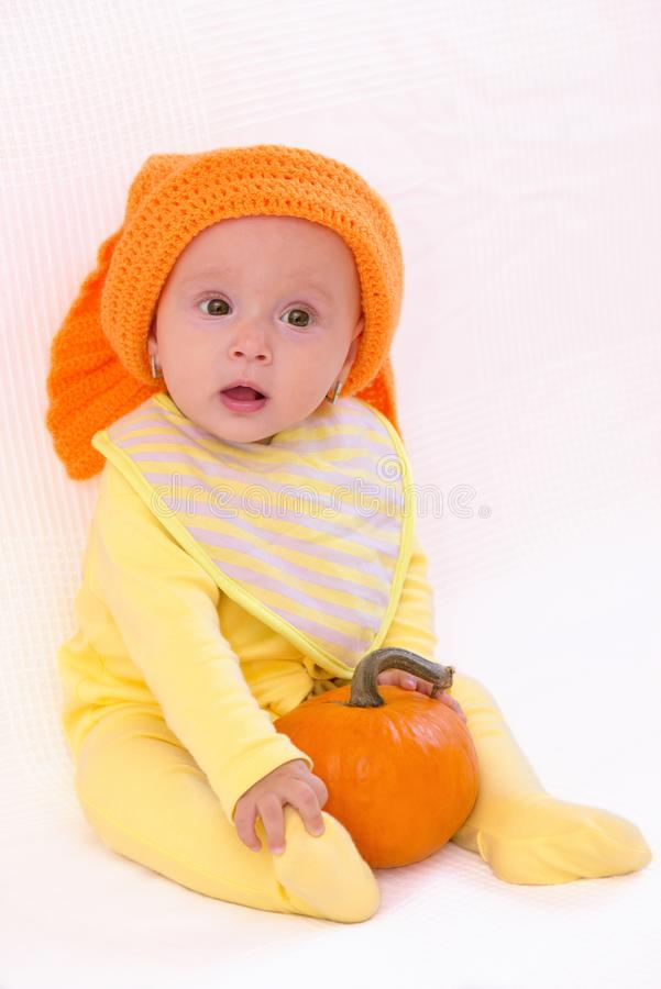 Cute baby girl with pumpkin and orange hat royalty free stock photos