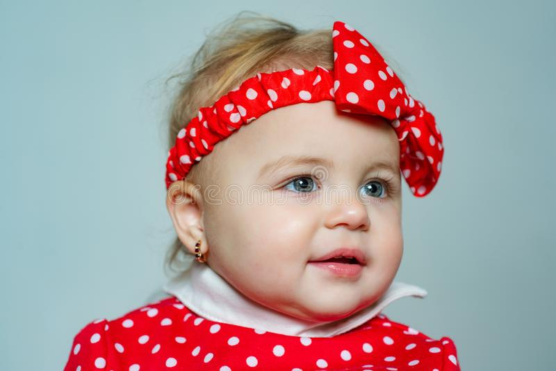 Cute baby girl red polka dot bow on head. Fashion accessory. Fashion for babies. Stylish toddler adorable girl. Happy. Childhood. Child care concept. Fashion royalty free stock photography