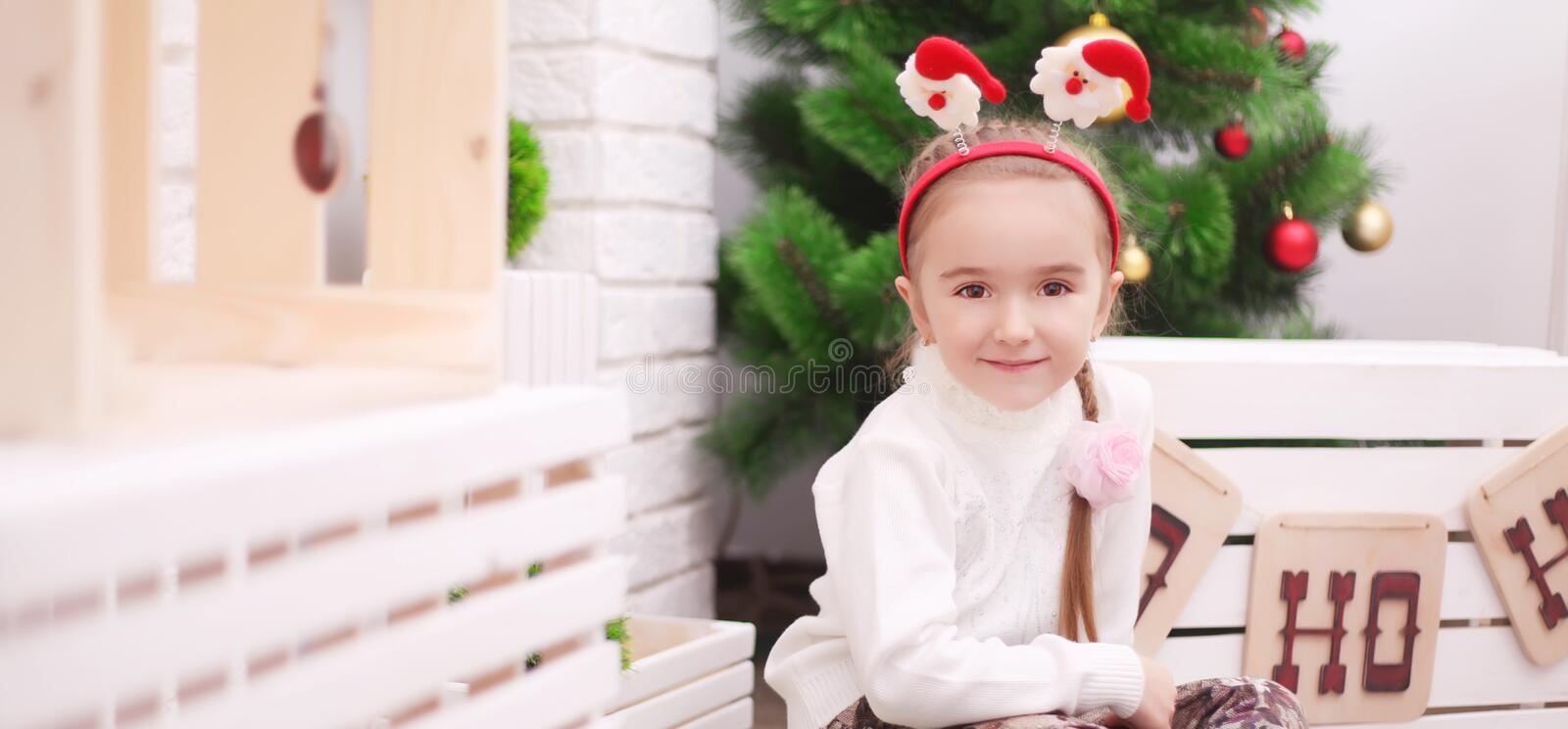 Cute baby girl sitting under christmas tree in room royalty free stock photography