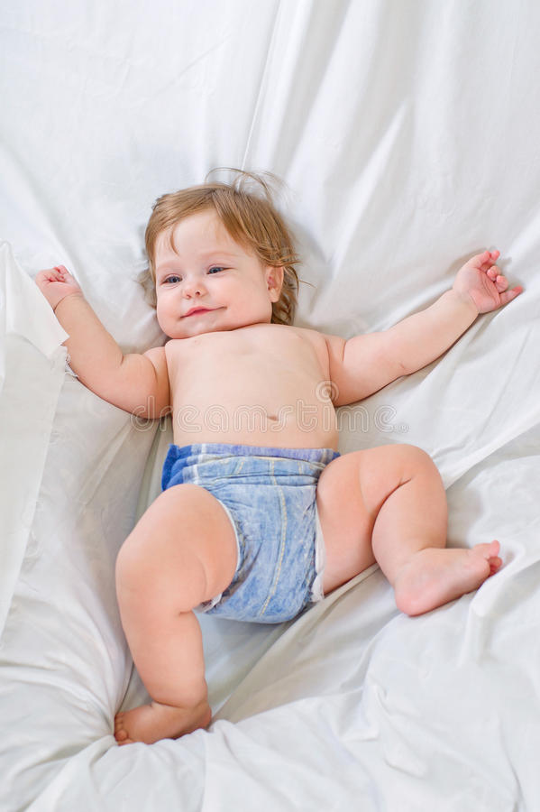 Cute baby girl smiles on white cloth stock photography