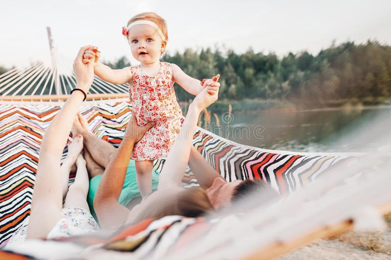 Cute baby girl in stylish dress with her parents lying in a hammock near lake and forest on family vacation trip, adorable hipster stock photography