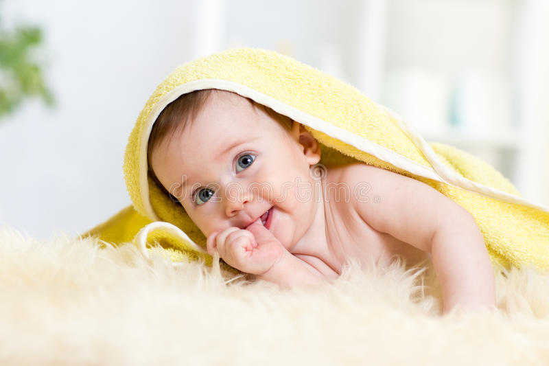 Cute baby girl sucking her thumb. Child lying under towel. royalty free stock image