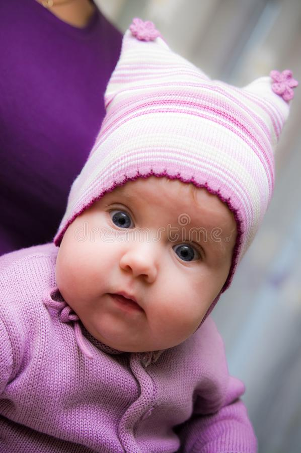 Cute baby girl wearing violet clothes. A cute baby girl wearing violet or purple clothes with her mother in the back stock photo