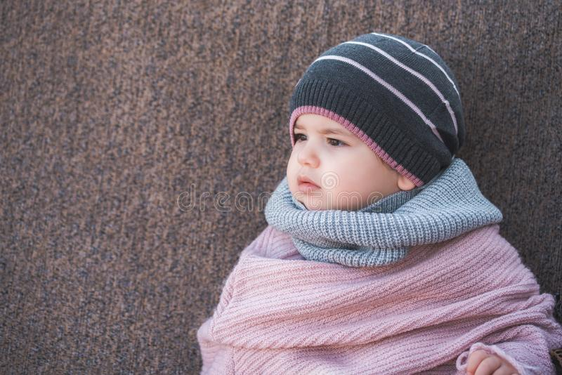 Cute baby girl wearing a warm winter hat and a colorful scarf on a brown background. royalty free stock image