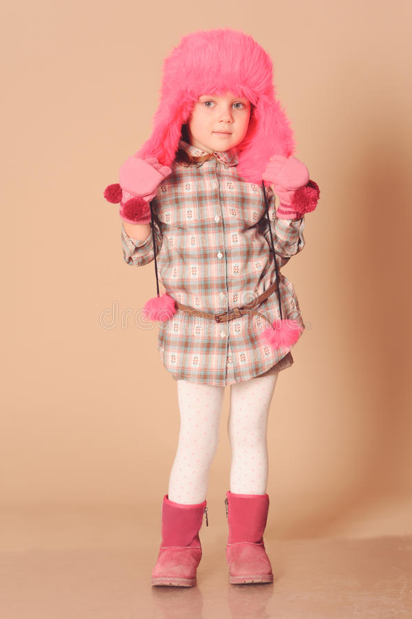 Cute baby girl wearing winter clothes. Closeup portrait of cute baby girl wearing winter clothes on beige stock photos