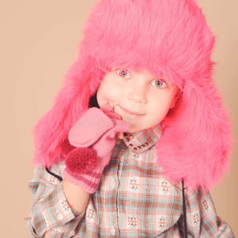 Cute baby girl wearing winter clothes. Closeup portrait of cute baby girl wearing winter clothes on beige royalty free stock images