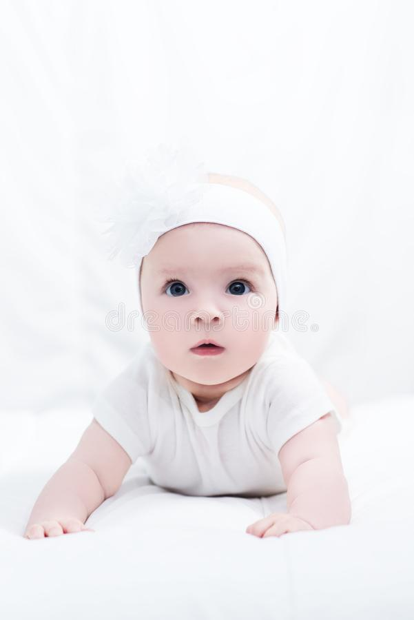 Portrait of cute little baby girl with bow flower on her head stock photo