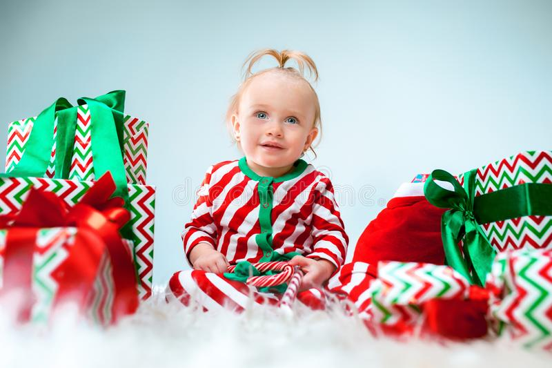 Cute baby girl 1 year old near santa hat posing over Christmas background. Sitting on floor with Christmas ball. Holiday royalty free stock image