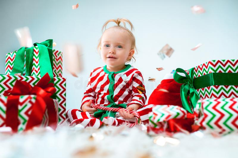 Cute baby girl 1 year old near santa hat posing over Christmas background. Sitting on floor with Christmas ball. Holiday stock images