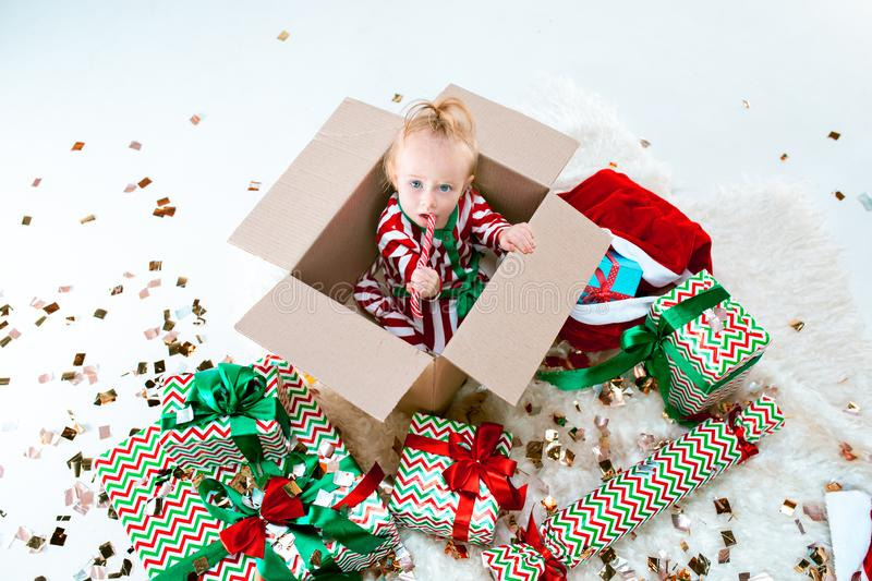 Cute baby girl 1 year old sitting at box over Christmas background. Holiday season. royalty free stock photography