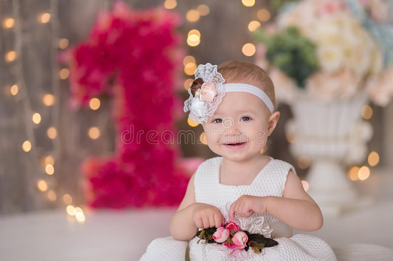 Cute baby girl 1-2 year old sitting on floor with pink balloons in room over white. Isolated. Birthday party. Celebration. Happy b. Irthday baby, Little girl royalty free stock photography