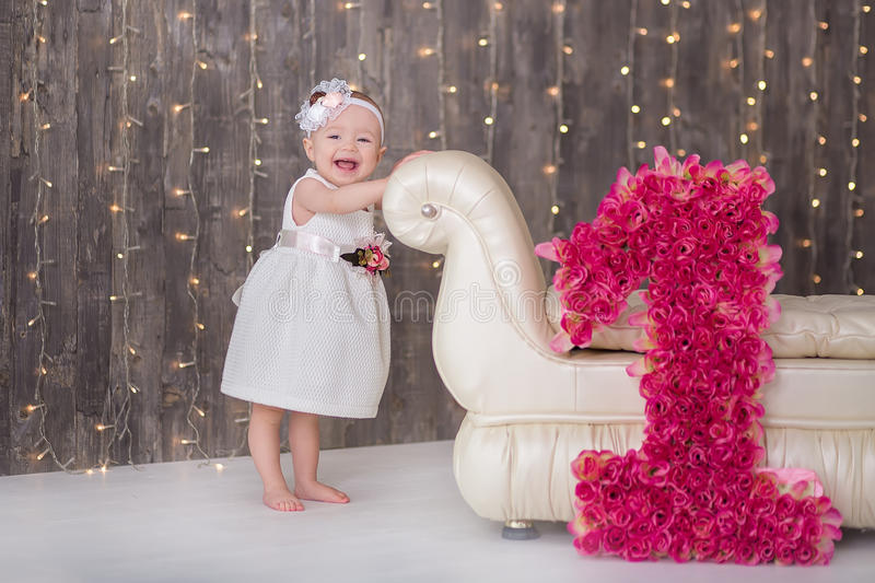 Cute baby girl 1-2 year old sitting on floor with pink balloons in room over white. Isolated. Birthday party. Celebration. Happy b stock photo