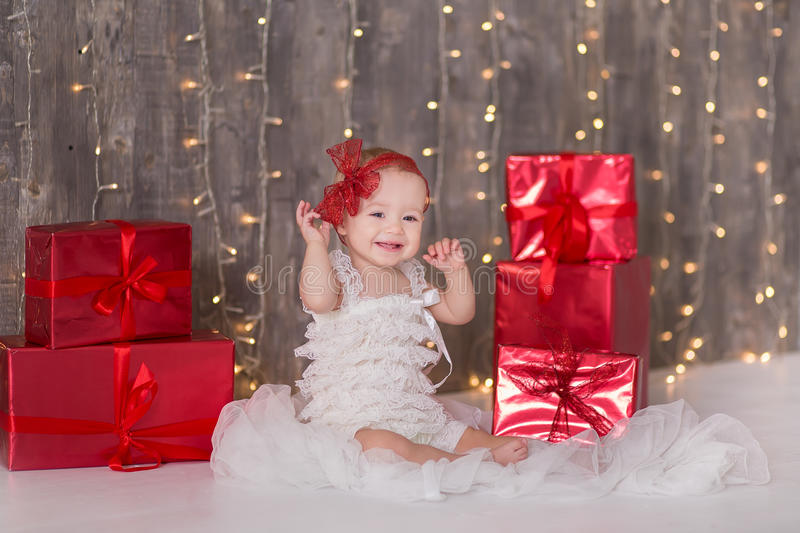 Cute baby girl 1-2 year old sitting on floor with pink balloons in room over white. Isolated. Birthday party. Celebration. Happy b stock photos