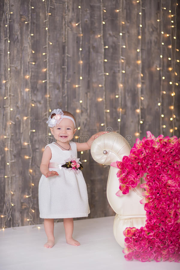 Cute baby girl 1-2 year old sitting on floor with pink balloons in room over white. Isolated. Birthday party. Celebration. Happy b royalty free stock photography