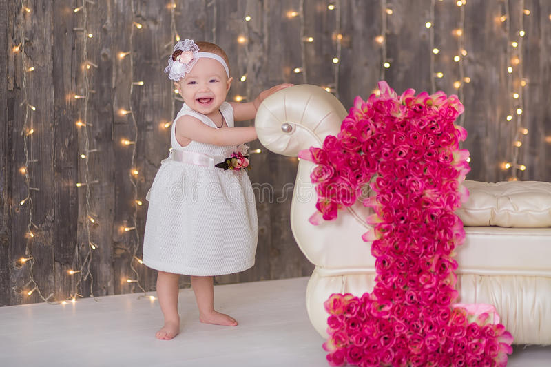 Cute baby girl 1-2 year old sitting on floor with pink balloons in room over white. Isolated. Birthday party. Celebration. Happy b royalty free stock image