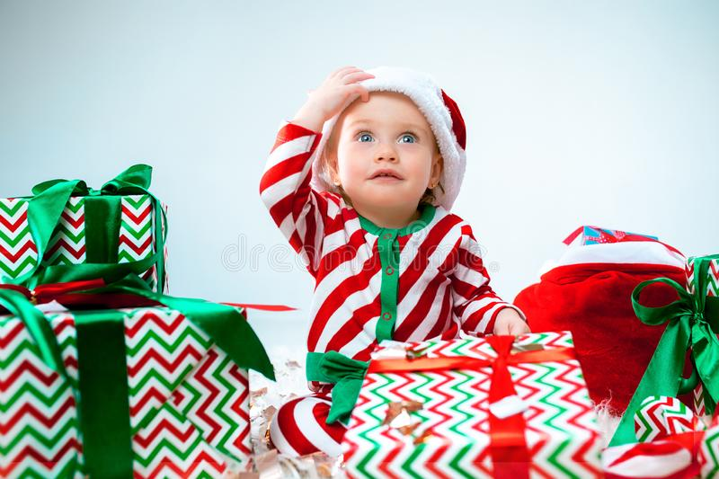 Cute baby girl 1 year old wearing santa hat posing over Christmas background. Sitting on floor with Christmas ball royalty free stock photography