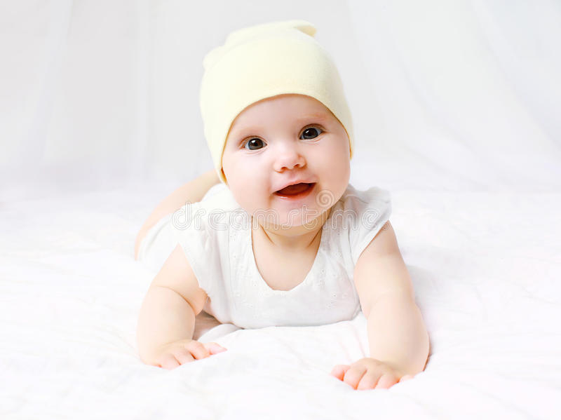 Cute baby in hat on the bed stock image