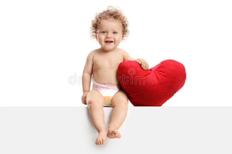 Cute baby with a heart shaped pillow sitting on a panel. Isolated on white background royalty free stock image