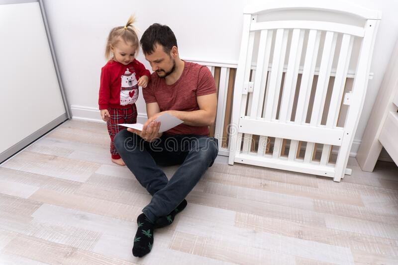 Father read manual how to assemble the crib. Cute baby help father to assemble cot, dad shows his child manual assembling the cradle stock photography