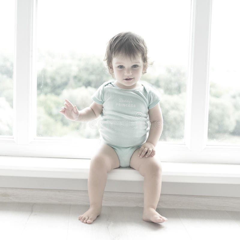 Cute baby at home in white room is sitting near window. The beautiful baby could be a boy or girl and is wearing body suit. Baby with curly hear is looking at stock images