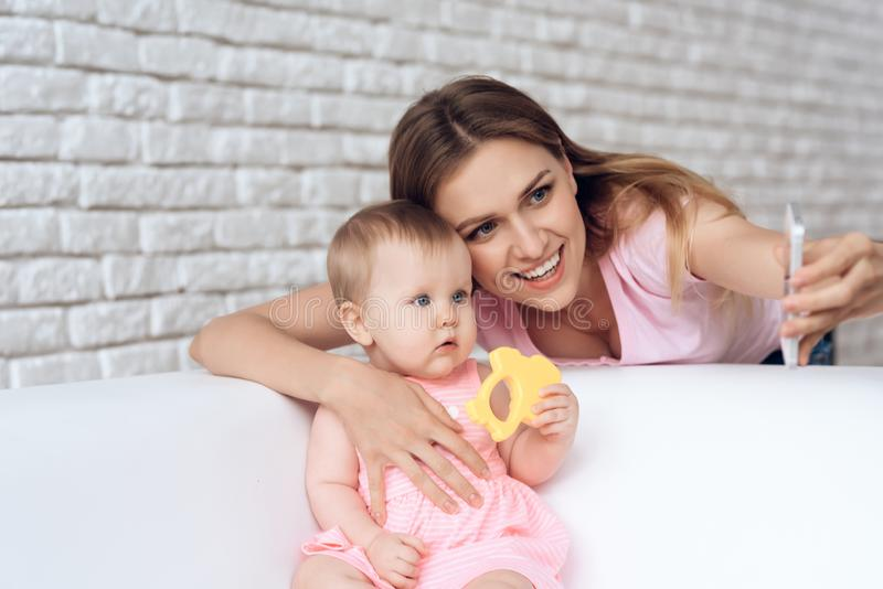 Cute baby hugging young smiling mother. royalty free stock image