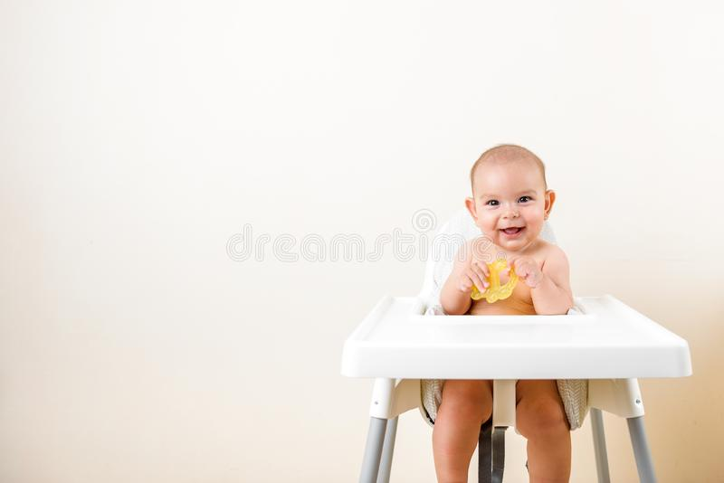 Cute baby infant kid biting sitting in highchair and chewing yellow eething toy copy space bright minimal healthcare. Cute baby infant kid biting sitting in royalty free stock photography