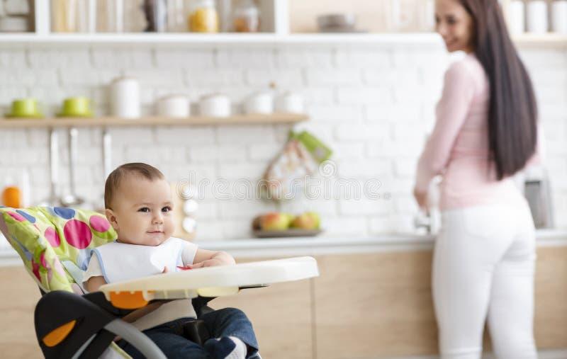 Cute baby leker på en hög stol i köket, moderdiskar. royaltyfri foto