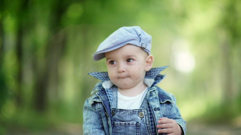 A cute baby. Little boy with apple. Toddler in denim suit and a cap stock photography