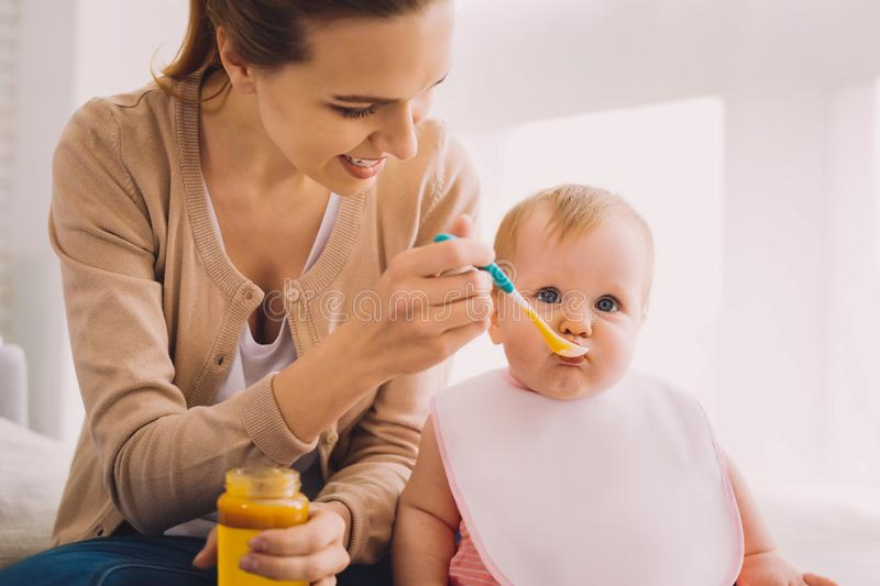 Cute baby looking calm while a babysitter feeding her. Healthy food. Cheerful reliable babysitter carefully feeding a serious toddler while holding a spoonful of royalty free stock images