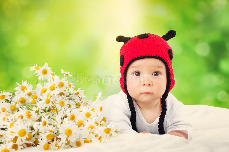 Cute baby lying in the bed on white blanket in ladybug hat royalty free stock photography