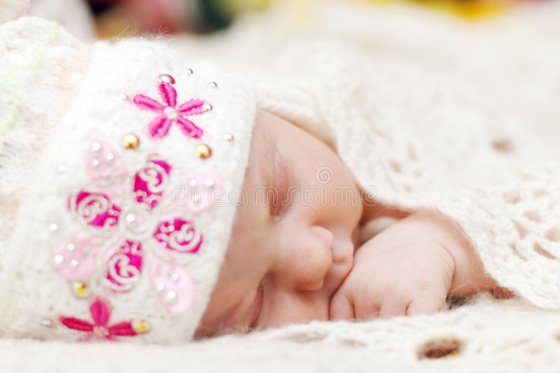 Cute baby lying in hat on bed under soft white knitted shawl royalty free stock images