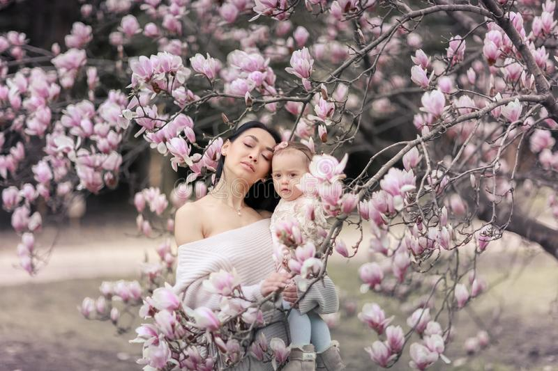 Cute Baby 6 month old Girl in Pink Outfit with Big Blue Eyes with Young Beautiful Mother at Spring, Pink Blooming Tree. At the Background royalty free stock photos