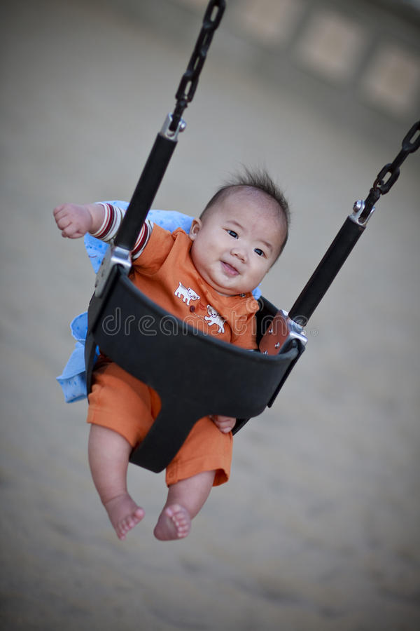 Cute baby on a playground swing