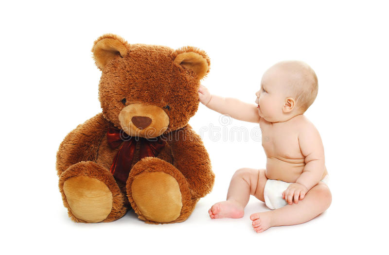 Cute baby playing with big teddy bear on white. Background royalty free stock image