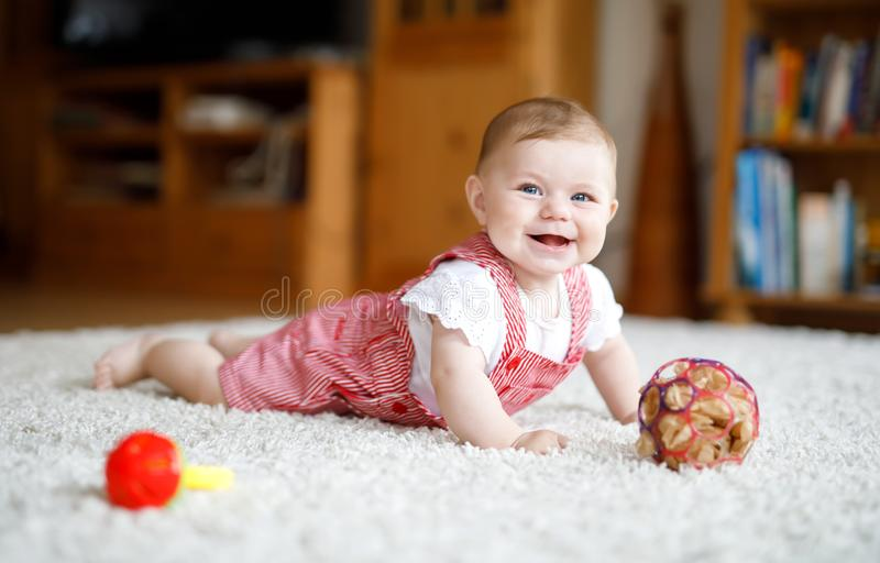 Cute baby playing with colorful rattle education toy. Lttle girl looking at the camera and crawling stock image