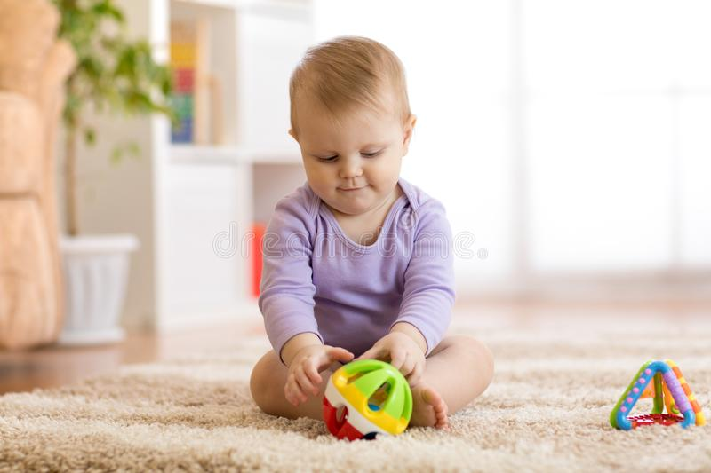 Cute baby playing with colorful toys sitting on carpet in white sunny bedroom. Child with educational toy. Early royalty free stock image