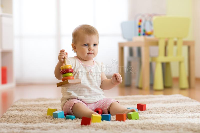 Cute baby playing with colorful toys sitting on carpet in white sunny bedroom. Child with educational toys. Early stock photography