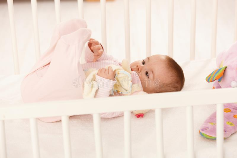 Cute baby playing with feet royalty free stock images