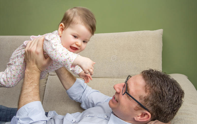 Cute baby playing with her happy father in a sofa. Cute baby portrait playing lying down with the hands of her happy father in a sofa at home stock images