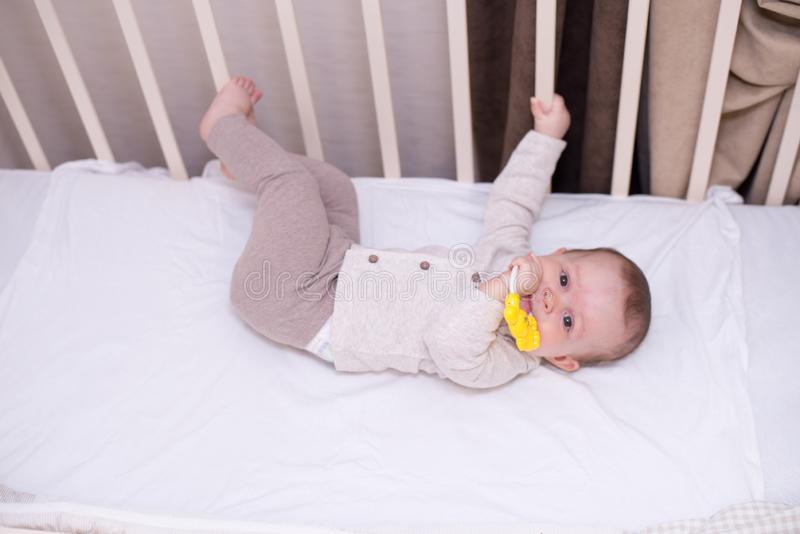 Cute baby playing with toy in bed . New born child, little girl having fun, . Family, childhood concept. copy space stock photos