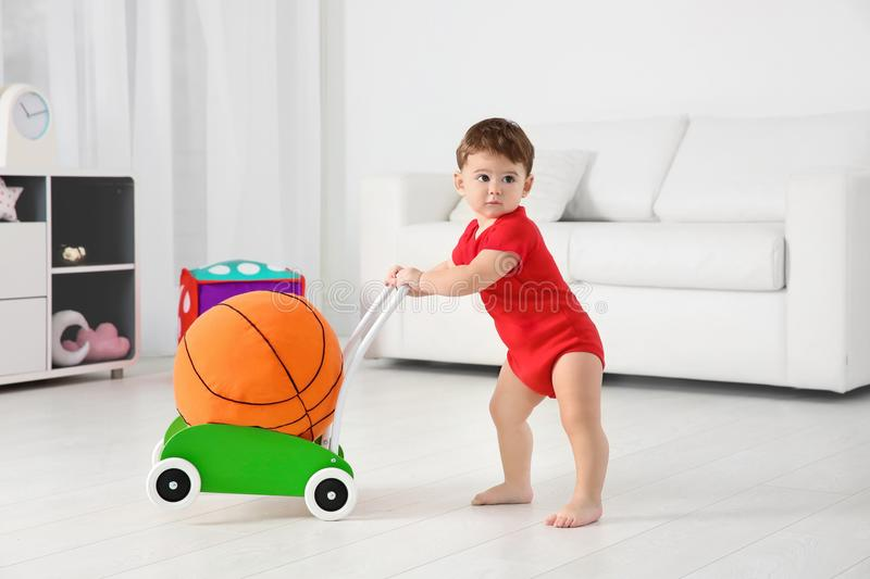 Cute baby playing with toy walker and ball. At home stock images