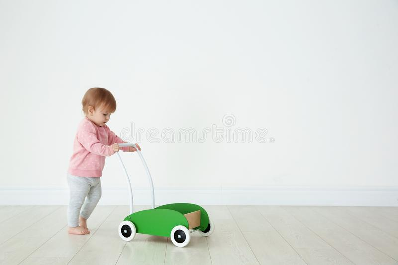 Cute baby playing with toy walker. Indoors stock photography