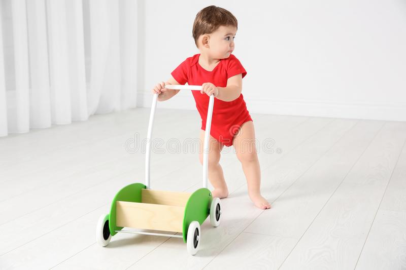 Cute baby playing with toy walker,. Indoors royalty free stock images