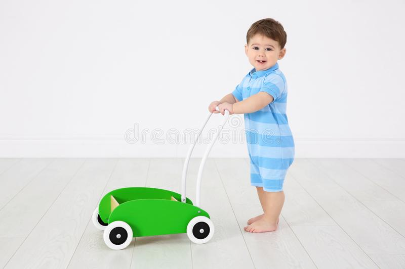 Cute baby playing with toy walker,. Indoors stock image