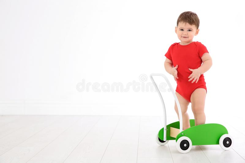 Cute baby playing with toy walker. Indoors stock images
