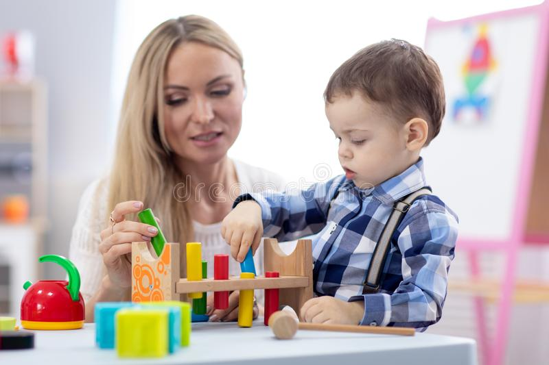 Cute baby playing with toys with teacher or mother indoors royalty free stock photo