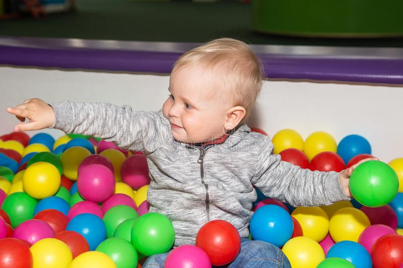 Cute baby plays with colorful balls in play ground. Ball pit poll at kids play center.  stock photos